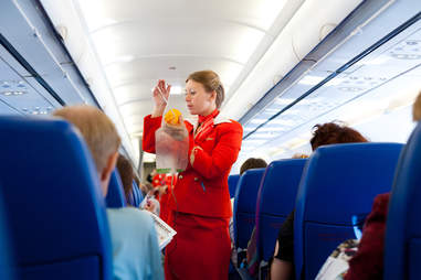 flight attendant demonstrating oxygen mask