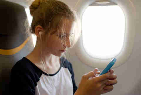 woman on an airplane with her cellphone