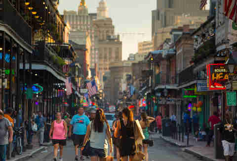 people walking down bourbon street in new orleans