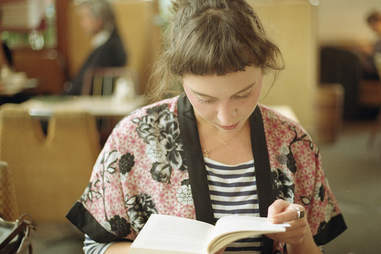Girl reading a book at a cafe
