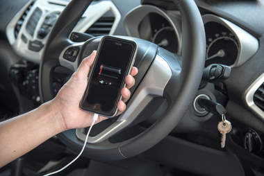 man charging dead iphone in car
