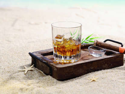 Glass of rum on a tray on a beach