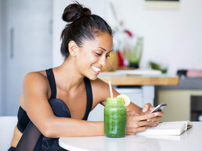girl on phone with green smoothie