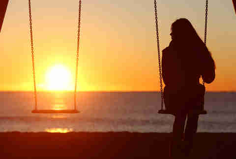 lonely woman on swings looking at sunset