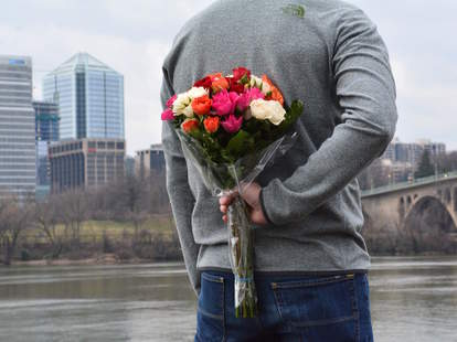 man apologizing with flowers, man holding flowers