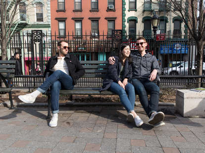 Couple sits on park bench while jealous friend watches