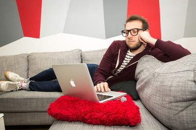 man relaxing on a couch with laptop