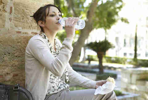woman drinking from a plastic water bottle