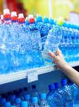 woman buying plastic water bottles