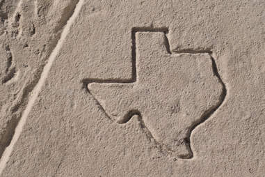 texas outlined in beach sand