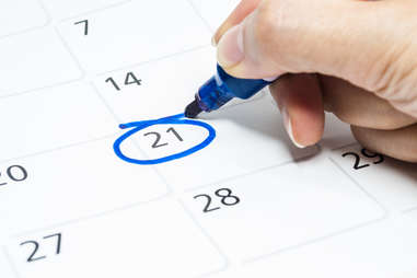 close up of person marking a date on a calendar