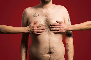 Shirtless man with hands covering his nipples
