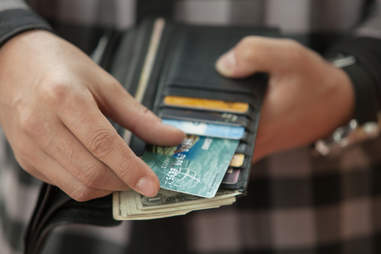 man with open wallet with credit cards and cash