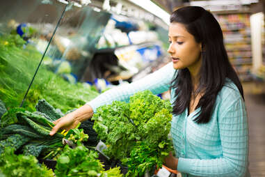 woman shopping for vegetables at a grocery store