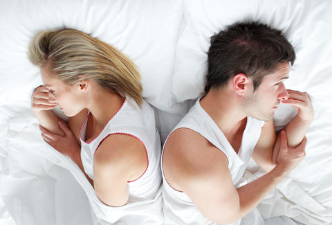 annoyed couple in bed together