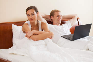 distracted man and annoyed woman in bed