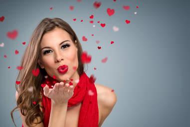 Woman blowing rose petals towards camera