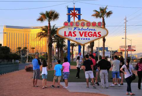 Tourists in front of Vegas welcome sign