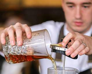 The Theodore's Kyle Hilla pouring a cocktail