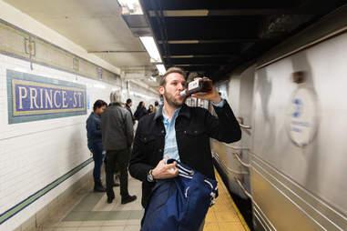 Man drinking whiskey as NYC subway passes