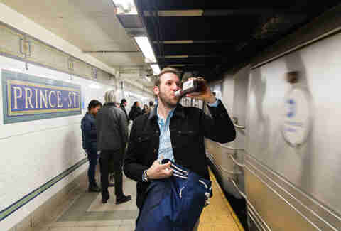 Man drinking whiskey as NYC subway passes