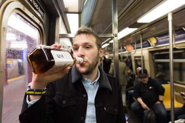 Man drinking whiskey within NYC subway
