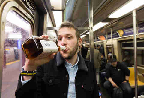 Man drinking whiskey within NYC subway