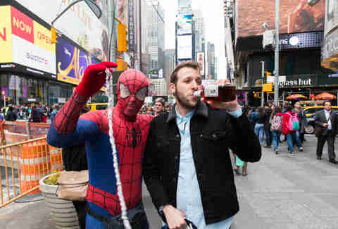 Man drinking whiskey with Times Square Spiderman