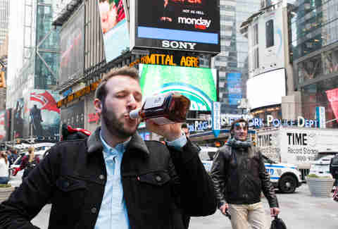 Man drinking whiskey in Times Square