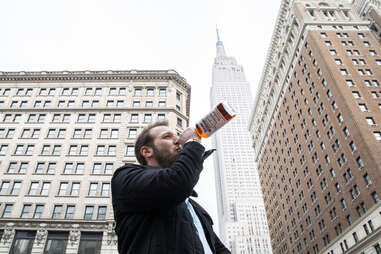 Man drinking in front of Empire State Building