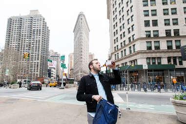 Man drinking in front of Flatiron Building