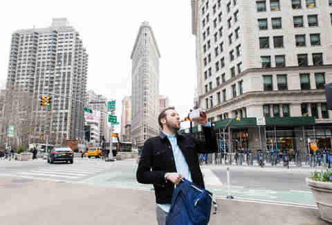 Man drinking in front of Flatiron Building