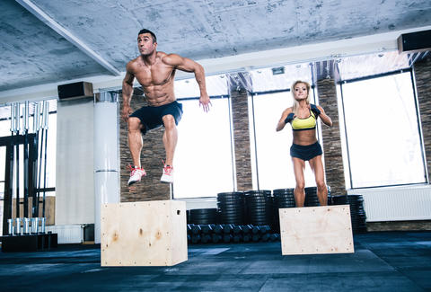 man and woman jumping on a fit box