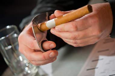 man cutting a cigar