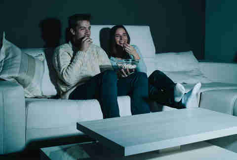 couple watching a movie on the couch with popcorn