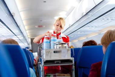 flight attendant serving coffee drinks beverage
