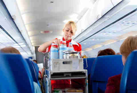 flight attendant serving coffee drinks beverage
