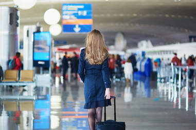 flight attendant in airport with luggage