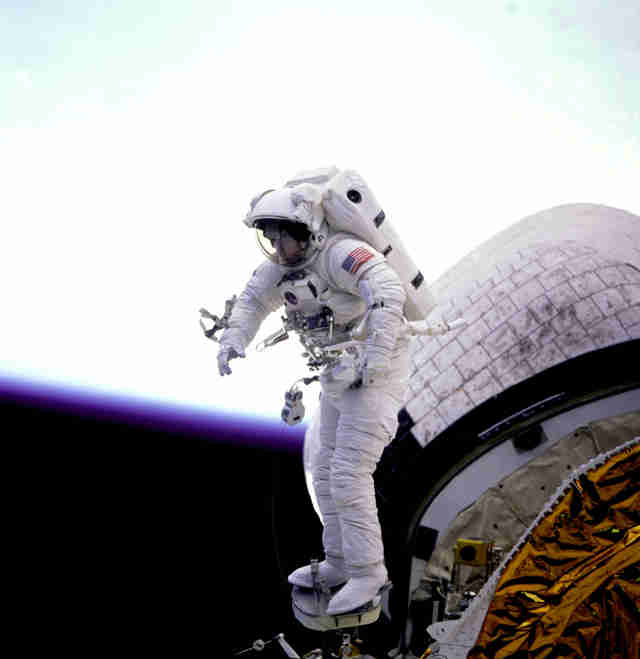 astronaut working outside shuttle discovery