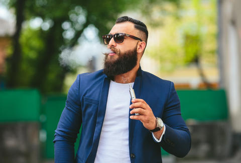 Bearded hipster man smoking vaporizer in public