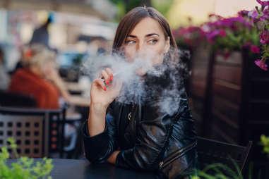 pretty woman smoking vaporizer in public