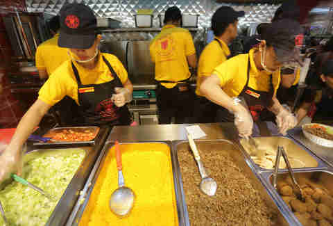 Woman working behind Halal Guys counter
