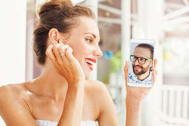 woman looking at man on smartphone