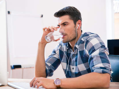 man drinking water and listening to music