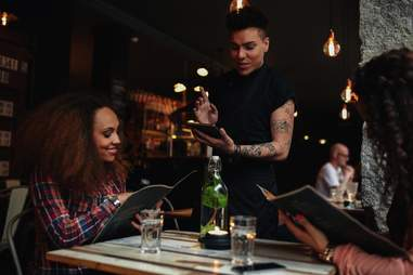 Waiter serving couple food