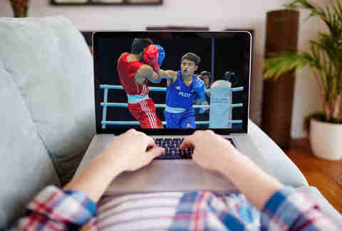 Man streaming boxing match on his Macbook laptop