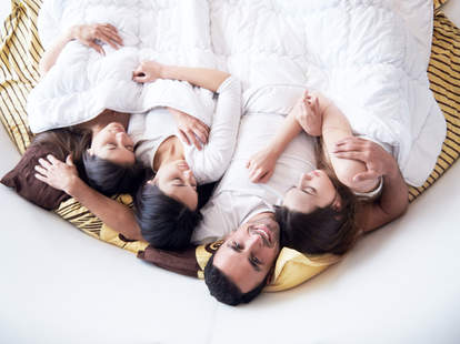 Man in bed with three women