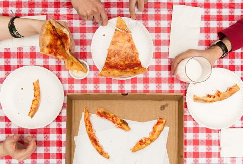 group eating cheese pizza on checkered tablecloth