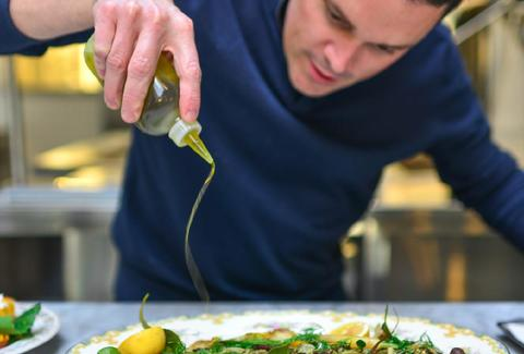 Spoon & Stable thrillist salad guy in blue shirt pouring olive oil