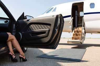 Woman climbing out of expensive car